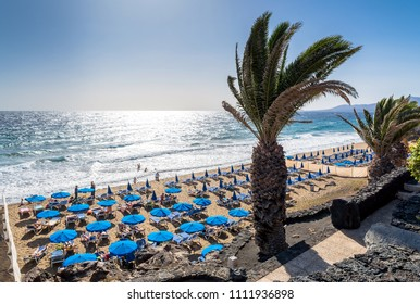 Puerto del Carmen, Spain - December 29, 2016: day view of beach with palm and tourists in Puerto del Carmen, Spain. Puerto del Carmen is the main tourist town on the island of Lanzarote