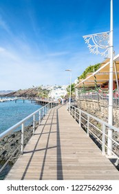 Puerto del Carmen, Spain - December 30, 2016: day view of ocean and boardwalk with tourists in Puerto del Carmen, Spain. Puerto del Carmen is the main tourist town on the island of Lanzarote.