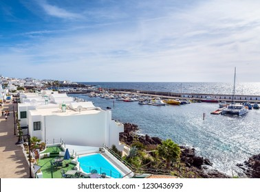 Puerto del Carmen, Spain - December 30, 2016: day view of old town and port boardwalk with tourists in Puerto del Carmen, Spain. Puerto del Carmen is the main tourist town on the island of Lanzarote