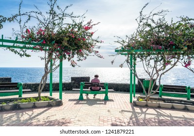 Puerto del Carmen, Spain - December 30, 2016: old town and port boardwalk with unidentified resting jogger in Puerto del Carmen, Spain. Puerto del Carmen is the main tourist town on Lanzarote island