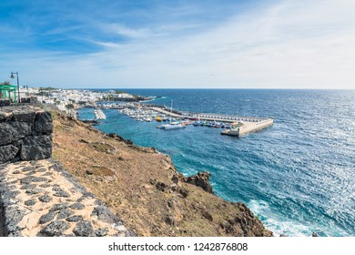 Puerto del Carmen, Spain - December 30, 2016: day view of old town and port boardwalk with tourists in Puerto del Carmen, Spain. Puerto del Carmen is the main tourist town on the island of Lanzarote.