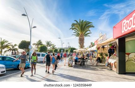 Puerto del Carmen, Spain - December 30, 2016: Avenida de las Playas street view with tourists in Puerto del Carmen, Spain. Avenida de las Playas is 7 km long and the main street in Puerto del Carmen.