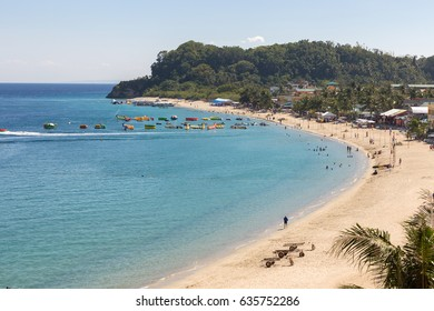 Puerto Galera, Philippines - April 4, 2017: Seascape of beach with transparent sea, blue sky, palms and boats.Taken Sabang, popular tourist and diving spot.