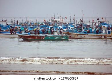 PUERTO LOPEZ, ECUADOR - CIRCA JULY 2018: Fleet of fishing boats moored off the beach