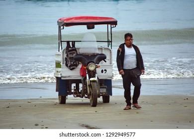 PUERTO LOPEZ, ECUADOR - CIRCA JULY 2018: Three wheeled moto scooter on the beach