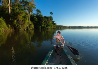 PUERTO MALDONADO, MADRE DE DIOS - PERU, CIRCA 2013: Instant of a unidentified man paddling his boat  in the river, Circa 2013 in Puerto Maldonado. The rivers are the main roads in the Amazon jungle.