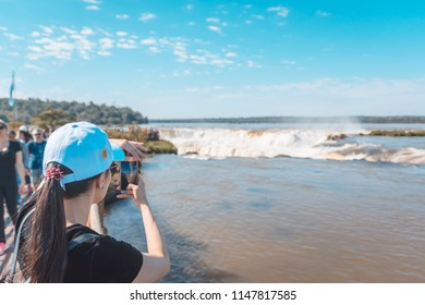 Puerto Iguazú, Misiones, Argentina. July 2018. Tourist photographing the Throat of the Devil in the Iguazu Falls seen by the Argentinean side.