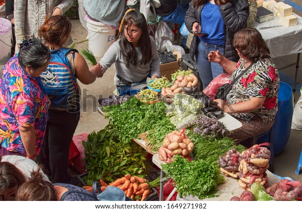 "Puerto Montt, Chile February 10, 2020: fruits and vegetables at a farmers market. ""Mercado Municipal Presidente Ibañez"". People buying natural products."