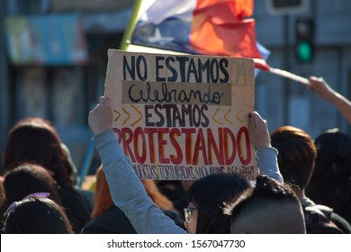 """Puerto Montt / Chile - November 20 2019: """"We are not celebrating, we are protesting"""". Chilean people in a massive protest at Puerto Montt. Protesters with chilean flag."""