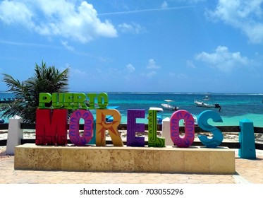 PUERTO MORELOS, RIVIERA MAYA, MEXICO - JULY 21, 2017: Colorful sign in Puerto Morelos, picturesque small coastal town on Riviera Maya, Mexico with turquoise Caribbean Sea on sunny summer day