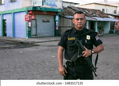 Puerto Parada, Usulután / El Salvador - November 22 2016: National police, policia national patrolling the town in his uniform. Carrying an assault rifle on his chest to fight against local gangs.