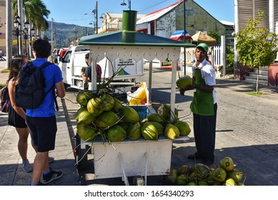 Puerto Plata, Dominican Republic - February 7, 2020:  A Dominican man cuts a coconut to sell the water to tourists in the Central Park, a popular tourist attraction.