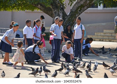Puerto Plata, Dominican Republic - January 22, 2014: Dominican school children in uniform feed the plentiful pigeons in the Central Park in Puerto Plata.