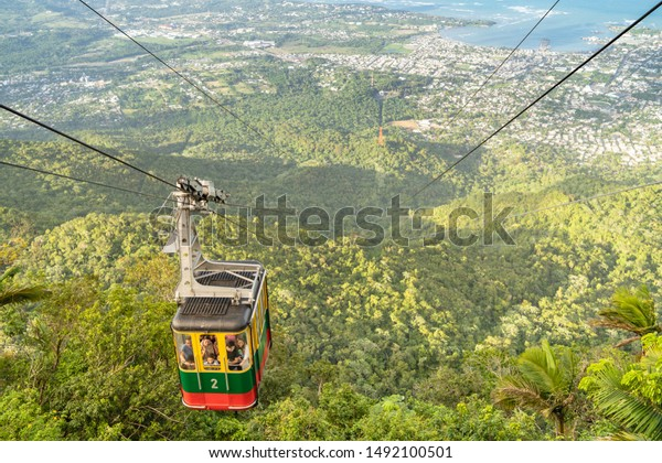 PUERTO PLATA/DOMINICAN REPUBLIC- DECEMBER 30, 2018: Cable car cabin in Loma Isabel de Torres mountain, with green mountain, Puerto Plata city and blue Caribbean sea in the background.