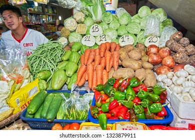 Puerto Princesa City, Palawan, Philippines - March 11, 2011: Young male vendor at a stall at the Central Market selling fresh vegetables, grocery