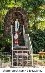 Puerto Princesa, Palawan, Philippines - March 3, 2019: Closeup of Lourdes style grotto outside White Immaculate Conception Cathedral against blue sky. Green foliage. Mary and Bernadette.