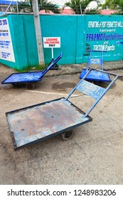 Puerto Princesa, Philippines-October 19, 2016: Blue painted-three wheeled pushcarts parked under loading-unloading only signboard placed beside the green concrete perimeter wall of the port facilities