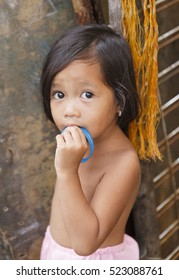 Puerto Princesa,Philippines-October 19,2016: Little girl plays in front of family trade on October 19, Palawan,Philippines.