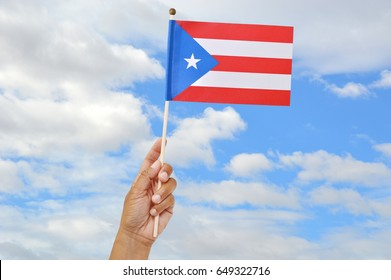 Puerto Rican Flag in hand blue sky clouds