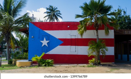 Puerto Rico flag painted on the side of a building adorned with different sized palm trees.