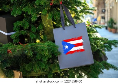 Puerto Rico flag printed on a Christmas shopping bag. Close up of a gift bag as a decoration on a Xmas tree on a street. New Year or Christmas shopping, local market sale and deals concept.
