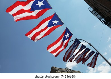 Puerto Rico flags flying over a Brooklyn street with a blue sky
