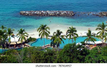 Puerto Vallarta, Jalisco/Mexico - January 2, 2018:  Turquoise water with beach side pool surrounded by palm trees.