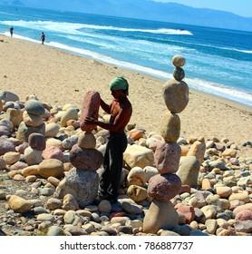Puerto Vallarta, Jalisco/Mexico - January 4, 2018:  Man creating stacked rock art displays for tips.