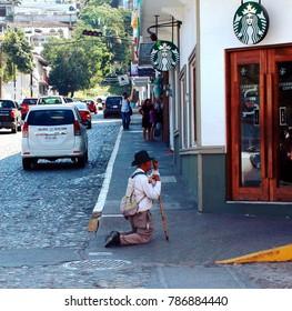 Puerto Vallarta Malecon Boardwalk, Jalisco/Mexico - January 4, 2018:  Man kneeling and praying on street corner