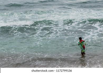 Puerto Vallarta Mexico 02/22/2017 Fisherman wading in the ocean at Los Muertos beach on Banderas Bay casting net.