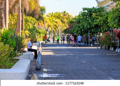 Puerto Vallarta Mexico 02/23/2017 Long shot of malecon cobblestone street walkway with man sitting on planter and jungle foliage.