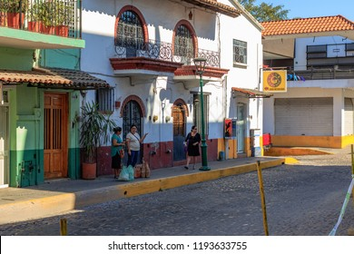 Puerto Vallarta Mexico 03/16/2017 Street scene of women waiting for bus in the shade in centro.