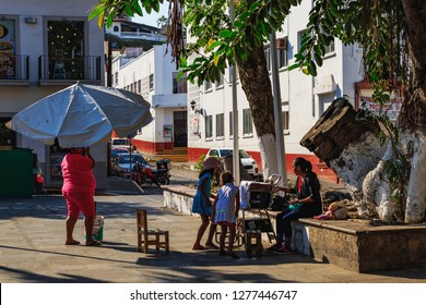 Puerto Vallarta Mexico 04/23/2017 Woman setting up umbrella at shoeshine chair in park at centro.