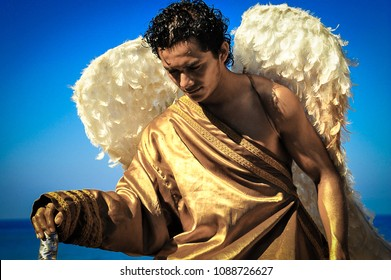 Puerto Vallarta, Mexico - January 2012: Handsome man poses as a living angel statue, dressed in gold costume with feathered wings.