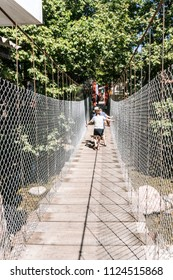 PUERTO VALLARTA, MEXICO - March 10 2018: Tourists walking along the unstable suspension bridge to Isla Rio Cuale from downtown Puerto Vallarta, MX-JAL.