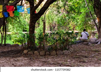Puerto Vallarta/Mexico 12/14/2016 Isla Cuale in Cuale River scene with mexican man sitting and facing away with colored streamers.