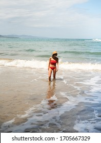 Puerto Viejo, Limon / Costa Rica - February 17,2020 - Beautiful blonde enjoying vacation in Costa Rica. International travel to a scenic Caribbean beach. Woman in fashionable red bathing suit.