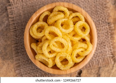 Puff corn rings in wooden bowl on burlap napkin. Snacks for watching movies. Copy space