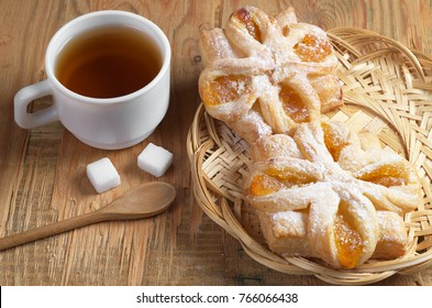 Puff pastries with orange jam in wicker plate and cup of tea on wooden background
