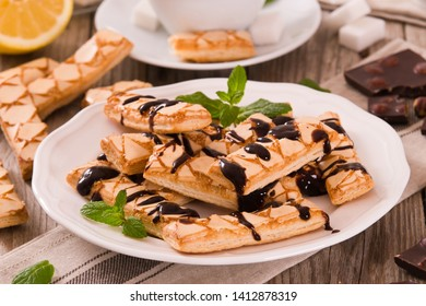 Puff pastry cookies with chocolate on white dish.