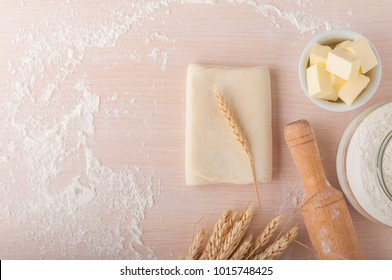 Puff pastry dough. Homemade folded raw puff pastry on a table. Making puff pastry. Dough's roll with a rolling pin, flour, butter, wheat spikelets with copy space.