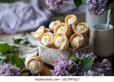 Puff pastry horns with vanilla cream in a metal box in spring still life with a bouquet of lilacs on a wooden table.