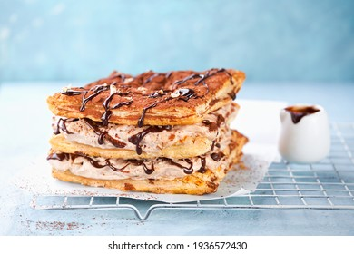Puff Pastry square cake with mocha whipped Cream or Chantilly and chocolate drip topping on light blue background. Copy space. Selective focus, close-up. Easy celebration desserts concept.