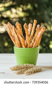 Puff pastry stick with poppy seeds in green bowl on wooden table
