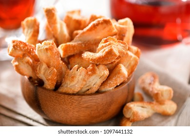 Puff pastry sticks cookies close-up in wooden bowl on table with  linen napkin