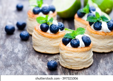 puff  pastry stuffed with soft cream cheese and blueberry with lime on rustic table