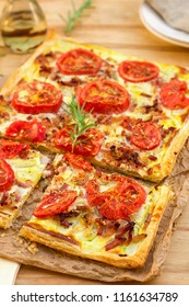 Puff pastry tart pizza style with tomatoes, zucchini, and bacon