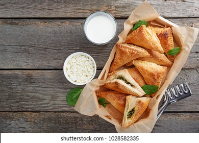Puff pastry triangles filled with feta cheese and spinach on wooden table.top view