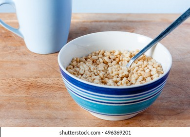 Puffed rice cereal in a striped blue bowl with a blue mug in the background