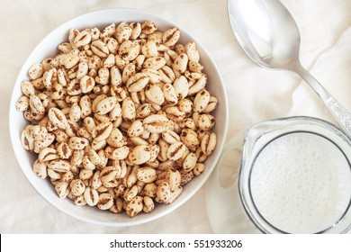 Puffed wheat cereal in white bowl with pitcher of milk and spoon. Top view